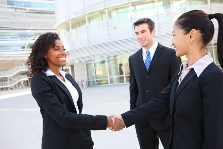 business interview: A diverse attractive man and woman business team handshake at office building Stock Photo