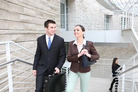 Business man and woman team walking up stairs at office building photo
