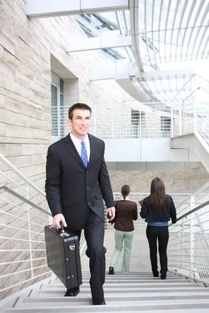 An attractive  business man walking up stairs at office building photo