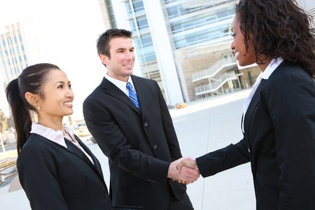 A diverse attractive man and woman business team handshake at office building Standard-Bild