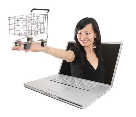 A pretty asian woman with shopping cart coming out of laptop computer photo
