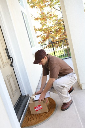 delivering: A young delivery man delivering a package to a house
