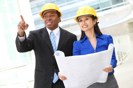 Een divers vrouw en de man aan het werk als architect op een bouw plaats (Focus op vrouw) Stockfoto