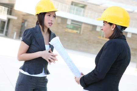 Two pretty diverse women architects on construction buidling site photo