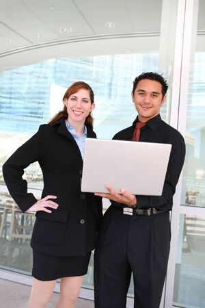 An attractive man and woman business team working on laptop computer outside office photo