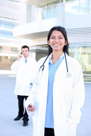 medical doctors: An Indian medical woman nurse outside hospital with man coworker in background
