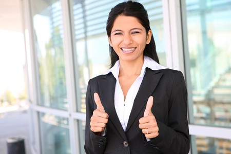 beautiful indian girl face: A pretty Indian business woman with thumbs up celebrating success