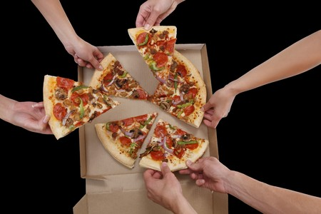 A group of people taking slices of pizza Stock Photo