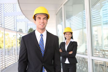 asian architect: A pretty woman and handsome man architects on building construction site