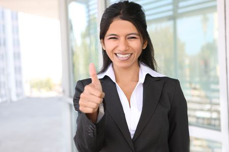 thumbs up: A pretty Indian business woman with thumbs up celebrating success