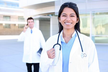 An Indian medical woman nurse outside hospital with man coworker in background Stock Photo - 8244864