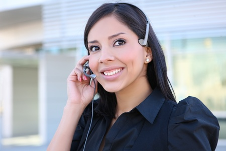 contact center: A pretty hispanic customer service business woman on the phone Stock Photo