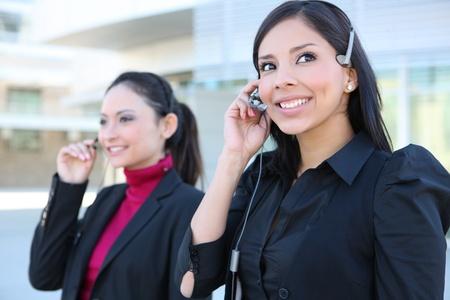 フレンドリーな秘書の女性はオフィス環境において電話ヘッドセット
