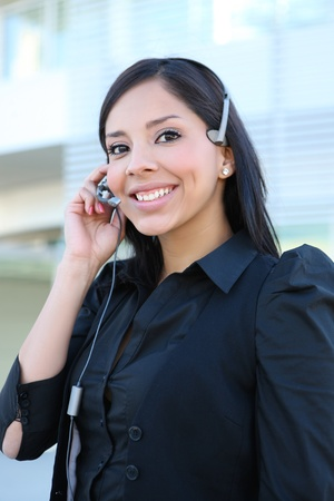 service: A pretty hispanic customer service business woman on the phone Stock Photo