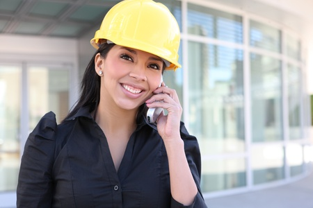 A young pretty hispanic woman architect with at building work site on phone photo