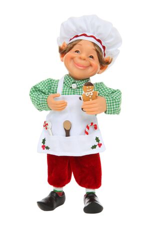 A cute young Christmas elf cooking gingerbread cookies