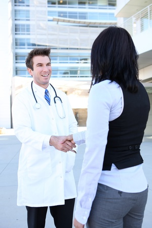 A man doctor and woman patient shaking hands outside hospital photo