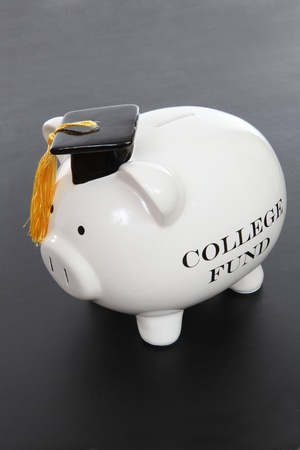 A piggy bank to act as a college fund over black background Stock Photo