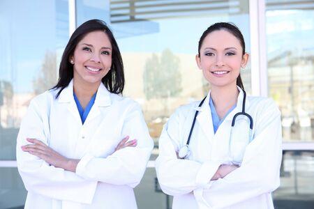 Two pretty young women nurses outside hospital smiling photo