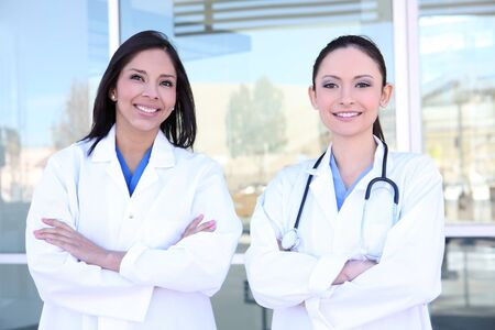 Two pretty young women nurses outside hospital smiling