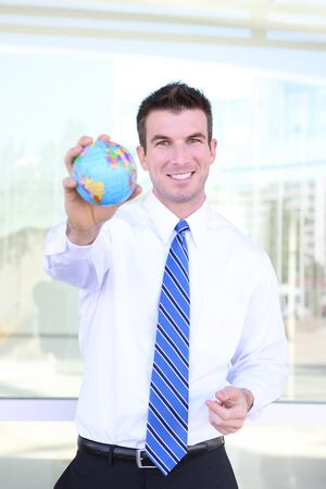 A handsome young business man holding a globe at office building