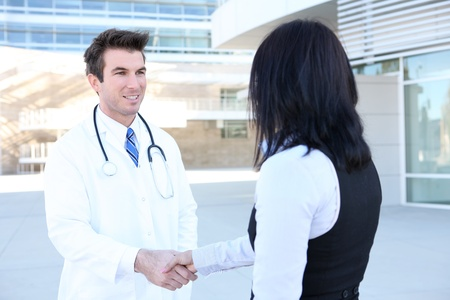 A man doctor and woman patient shaking hands outside hospital Stock Photo - 9028146
