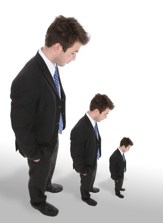 short: Three business men looking down as they get smaller