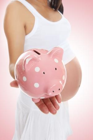 貯金を開催する妊娠中のママ 写真素材
