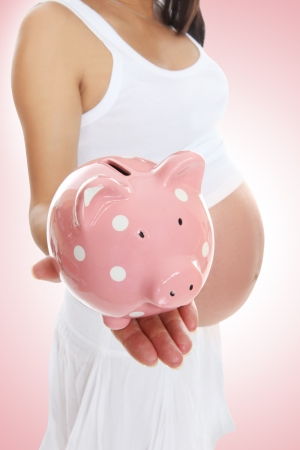 A pregnant mom to be holding a piggy bank