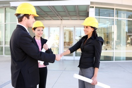 A handsome business man handshake with construction woman at office building photo