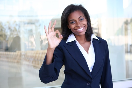 american staff: A pretty african american business woman signaling success at office