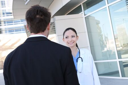 A pretty woman nurse with patient outside hospital photo