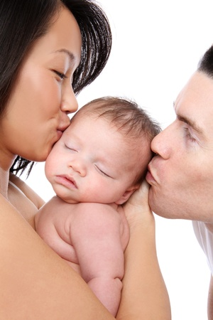A mom and dad parent kissing their young baby Stock Photo - 9389364
