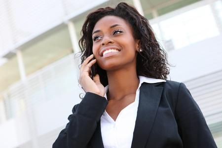 職場や学校での携帯電話上の美しいアフリカ人女性