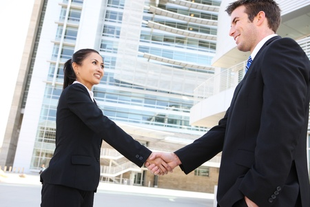 A pretty asian woman handshake with handsome man at office building photo