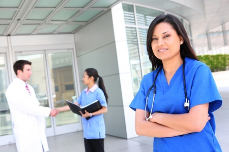 A pretty ethnic nurse outside hospital with team in background
