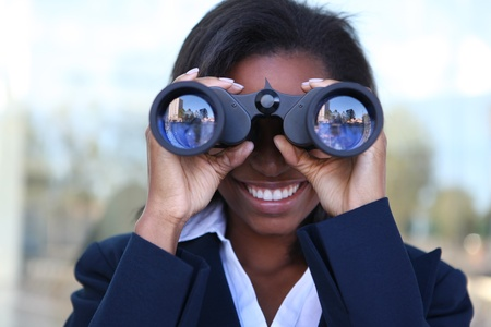 african american businesswoman: Beautiful african american business woman looking through binoculars