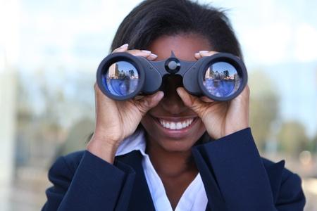 Beautiful african american business woman looking through binoculars