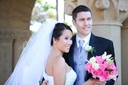 veil: Bride and Groom at church Wedding with flowers (FOCUS ON BRIDE)  Stock Photo
