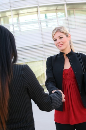 A beautiful young blonde business woman shaking hands photo