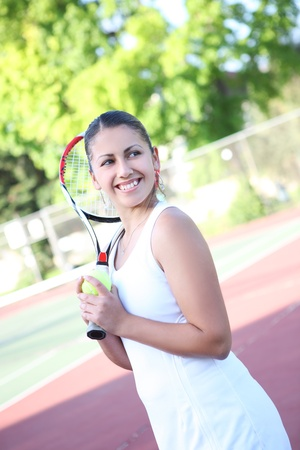 A pretty young woman tennis player getting ready to serve the ball