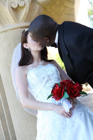 An  african man and caucasian woman wedding couple kissing outside church photo