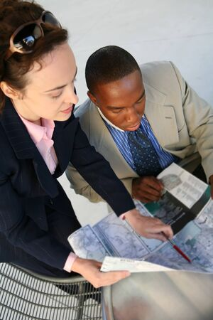 A diverse african man and caucasian woman at office looking at map
