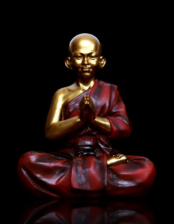 A religious spiritual golden monk statue praying over black photo