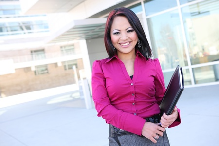 A pretty asian business woman with notebook at office building photo