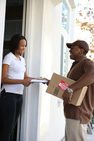 A handsome young delivery man delivering a package to house photo
