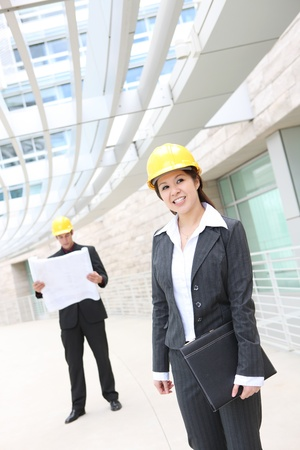 asian architect: A pretty woman asian architect on work site with male co-worker in background Stock Photo