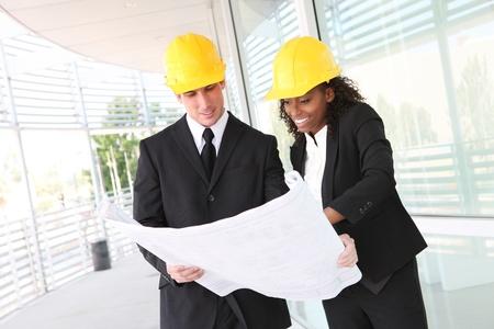 Een divers man en vrouw die werkt als architect op een bouwplaats  Stockfoto