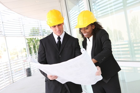 A diverse man and woman working as architect on a construction site  Archivio Fotografico