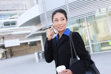 Portrait of pretty asian young  woman with phone at office building photo